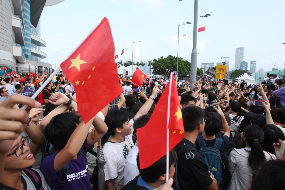 Young protesters wave a reversed Chinese national flag during a flag-raising ceremony where Hong Kong's embattled leader attended in Hong Kong, Wednesday, Oct. 1, 2014, to mark China's National Day. Leung attended the flag-raising ceremony Wednesday to mark China's National Day after refusing to meet pro-democracy demonstrators despite their threats to expand the street protests that have posed the stiffest challenge to Beijing's authority since China took control of the former British colony in 1997. The Chinese words read Step Down. (EyePress/Sunny Mok)